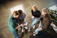 Молодые коллеги в офисе говоря друг с другом держащ тетрадь Стоковые Фото