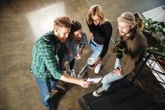 Молодые коллеги в офисе говоря друг с другом держащ тетрадь Стоковая Фотография RF