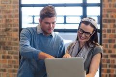 Молодые коллеги используя компьтер-книжку в офисе Стоковое Изображение RF