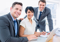 Молодые коллеги используя компьтер-книжку на столе офиса Стоковое Изображение