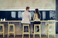 Молодые коллеги flirting в баре и говорить Стоковые Фото