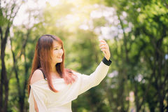 Молодые красивые азиатские женщины при длинные коричневые волосы принимая selfie на ее телефоне в парке Стоковые Изображения