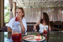 Молодые красивые девушки битника ослабляя совместно в кофейне, 2 привлекательных лучших другах женщин наслаждаясь остатками и хор Стоковое Изображение RF