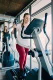 Молодые красивые девушки работая в спортзале с машиной лыжи Стоковые Изображения RF