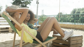 Молодые красивые девушки смешанной гонки сидя на sunbeds под зонтиком и наслаждаясь каникулами Стоковое фото RF