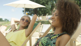 Молодые красивые девушки смешанной гонки сидя на sunbeds под зонтиком и наслаждаясь каникулами Стоковое Изображение