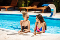 Молодые красивые девушки усмехаясь, говорить, ослабляя в бассейне Стоковое Изображение