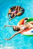 Молодые красивые девушки усмехаясь, загорающ, ослаблять, плавая в бассейне Стоковые Изображения RF