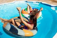 Молодые красивые девушки усмехаясь, загорающ, ослаблять, плавая в бассейне Стоковая Фотография