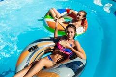 Молодые красивые девушки усмехаясь, загорающ, ослаблять, плавая в бассейне Стоковые Изображения