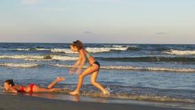 Молодые красивые женщины наслаждаясь дразнящ одно другое на красивом влажном песчаном пляже сток-видео