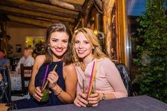 Молодые красивые женщины с коктеилями в баре или клубе Стоковые Фотографии RF