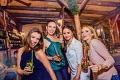 Молодые красивые женщины с коктеилями в баре или клубе Стоковые Фото