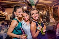 Молодые красивые женщины с коктеилями в баре или клубе Стоковая Фотография RF