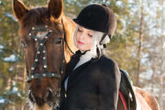 Молодые красивые жокей и лошадь девушки в лесе зимы Стоковая Фотография