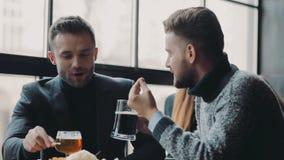 Молодые красивые мужские друзья имея активное обсуждение в баре спорта пока выпивающ пиво и ел обломоки неофициально видеоматериал