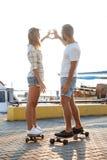 Молодые красивые пары идя на взморье, показывающ сердце, skateboarding Стоковая Фотография RF