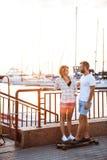 Молодые красивые пары идя на взморье, усмехающся, skateboarding Стоковые Изображения RF