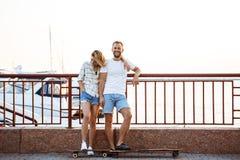 Молодые красивые пары идя на взморье, усмехающся, skateboarding Стоковое фото RF