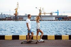 Молодые красивые пары идя на взморье, усмехающся, skateboarding Стоковые Фотографии RF