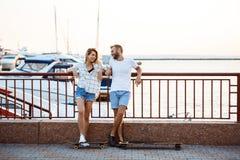 Молодые красивые пары идя на взморье, усмехающся, skateboarding Стоковая Фотография