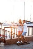 Молодые красивые пары идя на взморье, усмехающся, skateboarding Стоковое Изображение RF