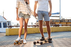 Молодые красивые пары идя на взморье, skateboarding Закройте вверх ног Стоковые Фото