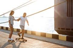 Молодые красивые пары идя на взморье, skateboarding Стоковые Изображения RF