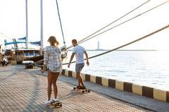 Молодые красивые пары идя на взморье, skateboarding Стоковые Фотографии RF