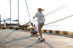 Молодые красивые пары идя на взморье, skateboarding Стоковое фото RF