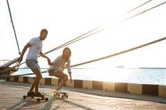 Молодые красивые пары идя на взморье, skateboarding Стоковое Фото