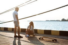 Молодые красивые пары идя на взморье, skateboarding Стоковые Изображения