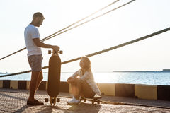 Молодые красивые пары идя на взморье, skateboarding Стоковое Изображение RF