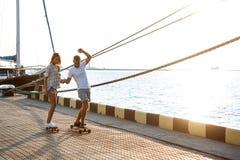 Молодые красивые пары идя на взморье, skateboarding Стоковое Изображение