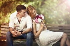 Молодые красивые пары сидя в парке и человеке предлагая wo Стоковые Изображения RF