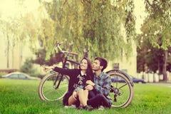 Молодые красивые пары сидя около винтажных велосипеда и указывать Стоковые Изображения