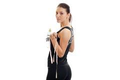 Молодые красивые стойки девушки спорта с его задней частью к камере и держат измеряя ленту и воду Стоковое фото RF