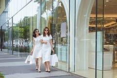 Молодые красивые счастливые женщины с хозяйственными сумками на улице на Стоковое Изображение