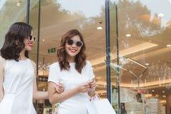 Молодые красивые счастливые женщины с хозяйственными сумками на улице на Стоковые Фото