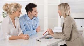 Молодые клиенты пар и советник или агент говоря о financ стоковое изображение rf