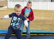 Молодые мальчики играя на батуте Стоковые Фотографии RF