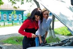 Молодые милые женщины на сломленном автомобиле Стоковые Изображения