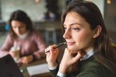 Молодые милые женщины работая с примечаниями и компьтер-книжкой в кафе Стоковое Изображение RF