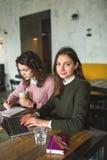 Молодые милые женщины работая с примечаниями и компьтер-книжкой в кафе Стоковые Изображения