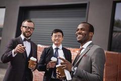 Молодые многонациональные бизнесмены в встрече formalwear на перерыве на чашку кофе outdoors Стоковое Изображение RF