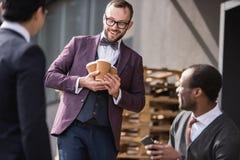 Молодые многонациональные бизнесмены в встрече formalwear на перерыве на чашку кофе outdoors Стоковые Фотографии RF