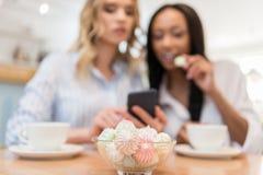 Молодые многонациональные женщины сидя на кафе и используя smartphone совместно Стоковые Фотографии RF