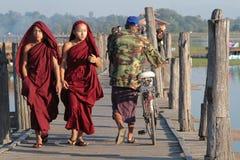 Молодые монахи на мосте U-Bein деревянном стоковые фото