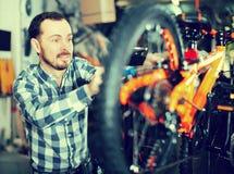 Молодые мужские части велосипеда держателей для собрания велосипед в магазине Стоковые Фотографии RF