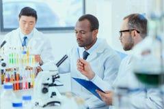 Молодые доктора в форме работая на испытательной лаборатории Стоковые Фото